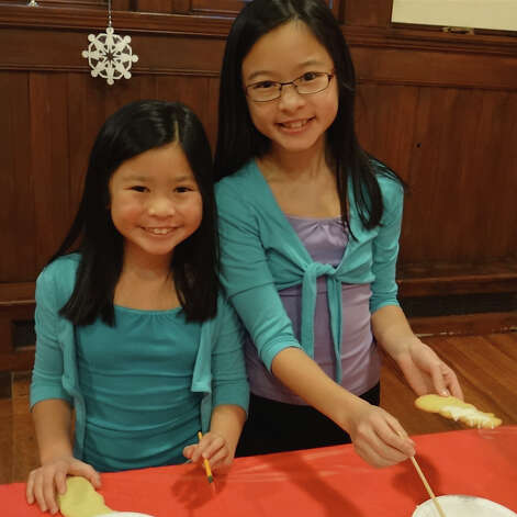 Sydney and Mikaela Woo, ages 8 and 10, of Fairfield, decorate snowman-shaped cookies at Pequot Library's holiday party.  Fairfield CT 12/21/12 Photo: Mike Lauterborn / Fairfield Citizen contributed