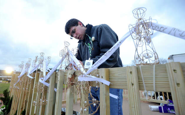Shane Price, of Newtown, works on decorations the stage in preparation for the vigil at Fairfield Hills Campus in Newtown on Friday, Dec. 21, 2012, one week after the shooting at Sandy Hook Elementary School. Price attended Sandy Hoo