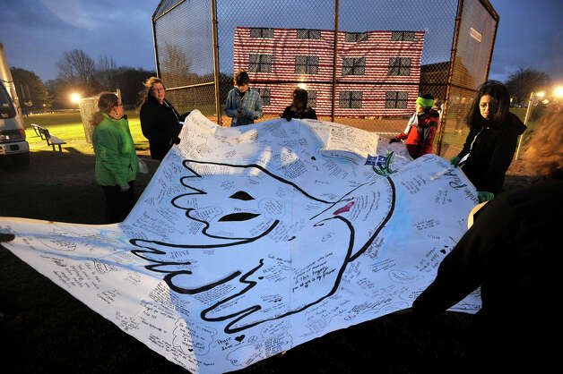 Volunteers errect a large banner displaying a dove in preparation for the vigil at Fairfield Hills Campus in Newtown on Friday, Dec. 21, 2012, one week after the shooting at Sandy Hook Elementary School. Photo: Jason Rearick / The News-Times