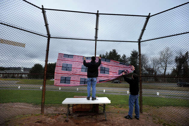 Volunteers errect an American flag-patterned display in preparation for the vigil at Fairfield Hills Campus in Newtown on Friday, Dec. 21, 2012, one week after the shooting at Sandy Hook Elementary School. Photo: Jason Rearick / The News-Times