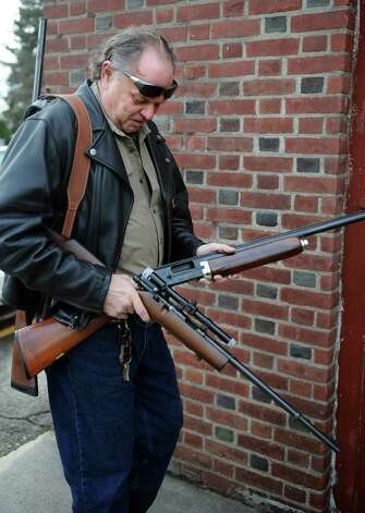 Bob Coyle, of East Haven, gets ready to turn in a rifle and a shotgun during a gun buyback event at the Bridgeport Police Department's Community Services Division Saturday, Dec. 22, 2012 in Bridgeport, Conn. In the wake of the tragedy in Newtown, Conn., the city raised $100,000 for the program and will offer up to $200 value for a working handgun, $75 for rifles and higher amounts for assault-type rifles. Photo: Autumn Driscoll / Connecticut Post
