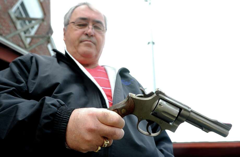 Kevin McMahon, of Bridgeport, gets ready to turn in his .38 Smith & Wesson revolver during a gun buyback event at the Bridgeport Police Department's Community Services Division Saturday, Dec. 22, 2012 in Bridgeport, Conn. In the wake of the tragedy in Newtown, Conn., the city raised $100,000 for the program and will offer up to $200 value for a working handgun, $75 for rifles and higher amounts for assault-type rifles.  McMahon was issued the service revolver June 20, 1974. Photo: Autumn Driscoll / Connecticut Post