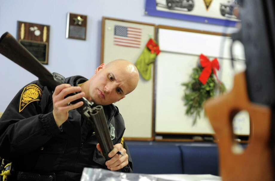 Police Officer Rick Lopez registers a rifle during a gun buyback event at the Bridgeport Police Department's Community Services Division Saturday, Dec. 22, 2012 in Bridgeport, Conn. In the wake of the tragedy in Newtown, Conn., the city raised $100,000 for the program and will offer up to $200 value for a working handgun, $75 for rifles and higher amounts for assault-type rifles. Photo: Autumn Driscoll / Connecticut Post