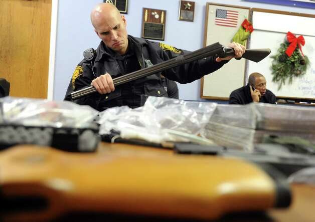 Police Officer Rick Lopez registers a shotgun during a gun buyback event at the Bridgeport Police Department's Community Services Division Saturday, Dec. 22, 2012 in Bridgeport, Conn. In the wake of the tragedy in Newtown, Conn., the city raised $100,000 for the program and will offer up to $200 value for a working handgun, $75 for rifles and higher amounts for assault-type rifles. Photo: Autumn Driscoll / Connecticut Post