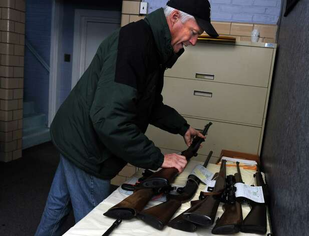 Bridgeport Mayor Bill Finch sets aside a turned in rifle during a gun buyback event at the Bridgeport Police Department's Community Services Division Saturday, Dec. 22, 2012 in Bridgeport, Conn. In the wake of the tragedy in Newtown, Conn., the city raised $100,000 for the program and will offer up to $200 value for a working handgun, $75 for rifles and higher amounts for assault-type rifles. Photo: Autumn Driscoll / Connecticut Post
