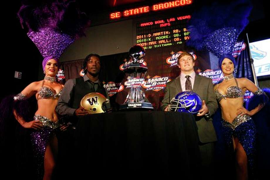 Washington's Desmond Trufant, center left, and Boise State's J.C. Percy, center right, pose with showgirls during a news conference at the New York-New York Hotel and Casino, Thursday, Dec. 6, 2012, to announce details of their MAACO Bowl Las Vegas NCAA college football game in Las Vegas. The two schools are scheduled to play each other Dec. 22. Photo: Jessica Ebelhar, AP / Las Vegas Review-Journal