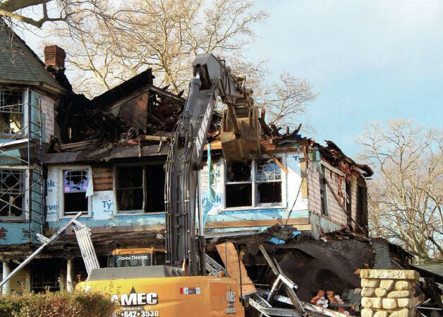 A demolition crew from Norwalk-based AMEC tears down the house at 2267 Shippan Ave. on Dec. 26 -- a day after a fire tore through the house killing five people. Photo: Contributed Photo / Stamford Advocate Contributed