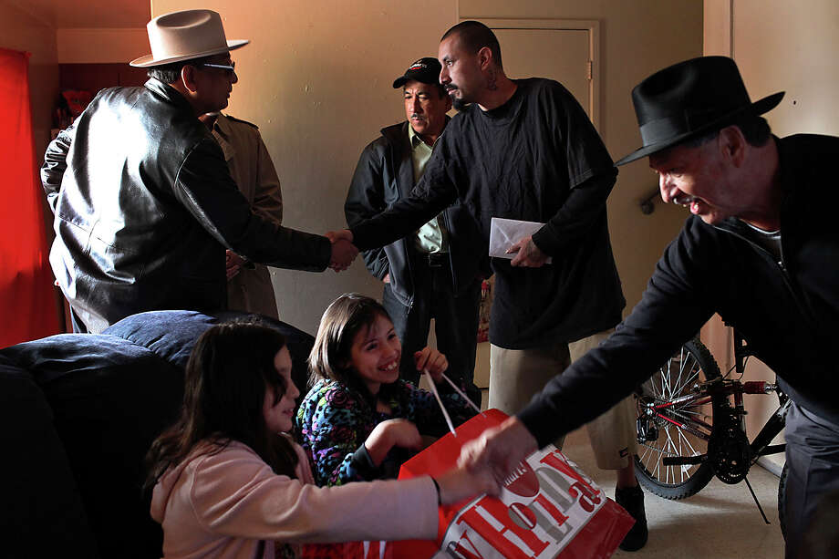Raymond Gonzalez (center) greets Juan Guajardo (from left) Alfred Palacio (obscured) and Hector Caldera while Leonardo Mendez (right) talks with Gonzalez's daughters, Anastasia (foreground) and Anna. Photo: Lisa Krantz, San Antonio Express-News / © 2012 San Antonio Express-News