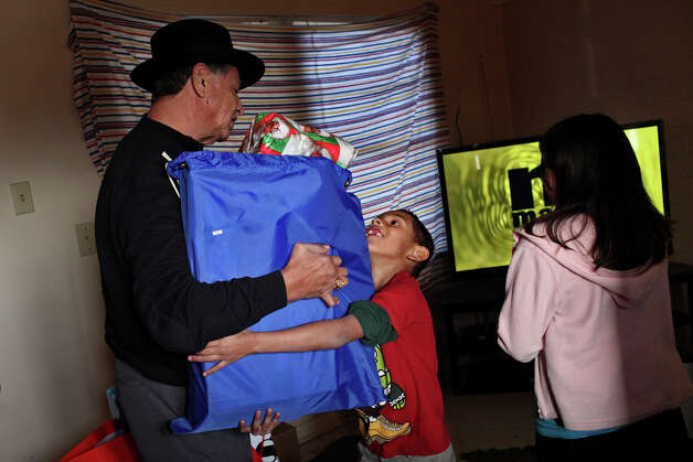 Mendez hands a bag of presents to Sebastian Gonzalez, 7, as his sister, Anastasia, 10, watches at their apartment in the Cassiano Homes. Photo: Lisa Krantz, San Antonio Express-News / © 2012 San Antonio Express-News