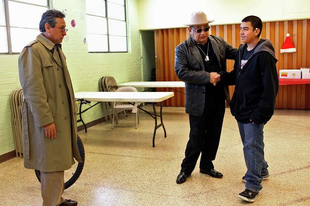 Ghost Town survivors Alfred Palacio, left, and Juan Guajardo greet Francisco Gonzales, 14, as they present him with a bicycle at the Good Samaritan Center in San Antonio on Thursday, Dec. 20, 2012. Photo: Lisa Krantz, San Antonio Express-News / © 2012 San Antonio Express-News