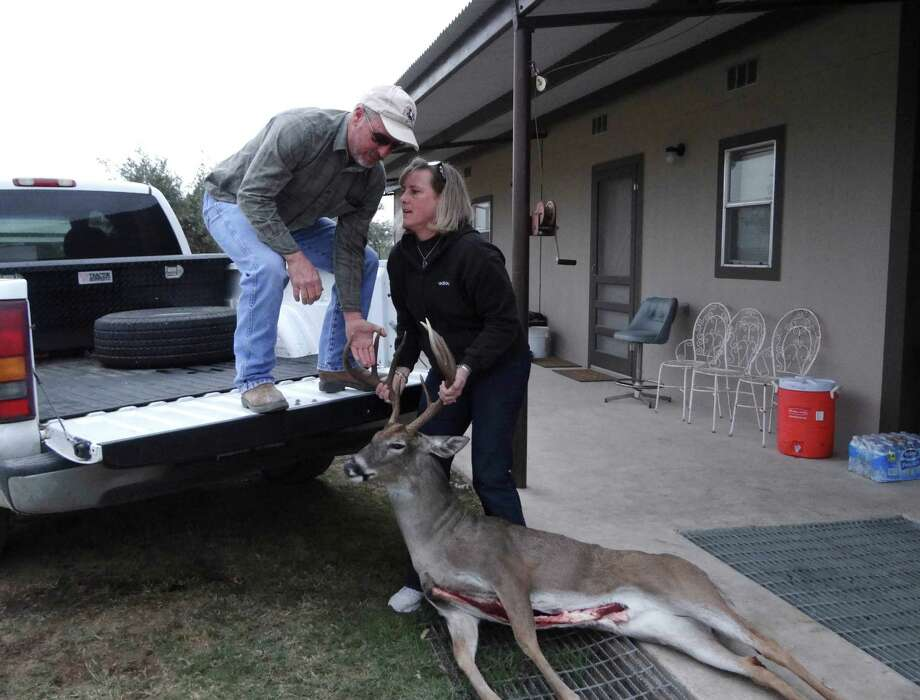 Terry Retzloff helps wife Annmarie load a harvested deer to have it taken to be processed. The Retzloff family offers hunting excursions on their ranch property. Photo: Billy Calzada, San Antonio Express-News / SAN ANTONIO EXPRESS-NEWS