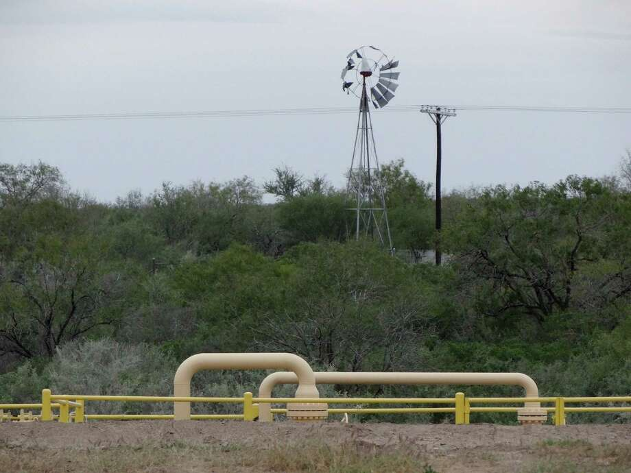 Pipes, part of the Eagle Ford Shale hydraulic fracturing energy industry, run by a broken windmill in Live Oak County, South Texas, on Thursday, Dec. 13, 2012. Photo: Billy Calzada, San Antonio Express-News / SAN ANTONIO EXPRESS-NEWS