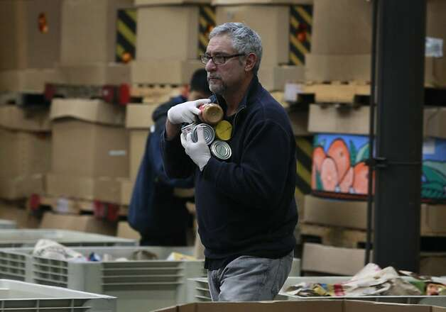Stuart Koplowitz carries donated food to separate bins at the San Francisco Food Bank in San Francisco, Calif. on Saturday, Dec. 22, 2012. Photo: Paul Chinn, The Chronicle