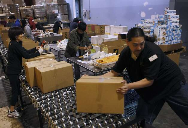 Employee Robert Alvarez stacks emergency food boxes that are packed by volunteers, including Oanh Le (left), who's assignment was sealing each box, at the San Francisco Food Bank in San Francisco, Calif. on Saturday, Dec. 22, 2012. Photo: Paul Chinn, The Chronicle