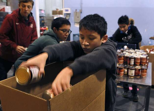 Alexander Esquivel-Cheung and other members of Boy Scout Troop 333 volunteer to help pack food for the holidays. Photo: Paul Chinn, The Chronicle