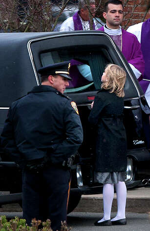 A little girl looks into the hearse carrying the casket of Josephine Gay after her funeral at St. Rose of Lima Roman Catholic Church, Saturday, Dec. 22, 2012, in Newtown. Gay was one of 26 killed after gunman Adam Lanza opened fire killing 26 individuals, 20 whom were children, at Sandy Hook Elementary School last Friday. Photo: Cody Duty, Cody Duty/Hearst Newspapers / The News-Times