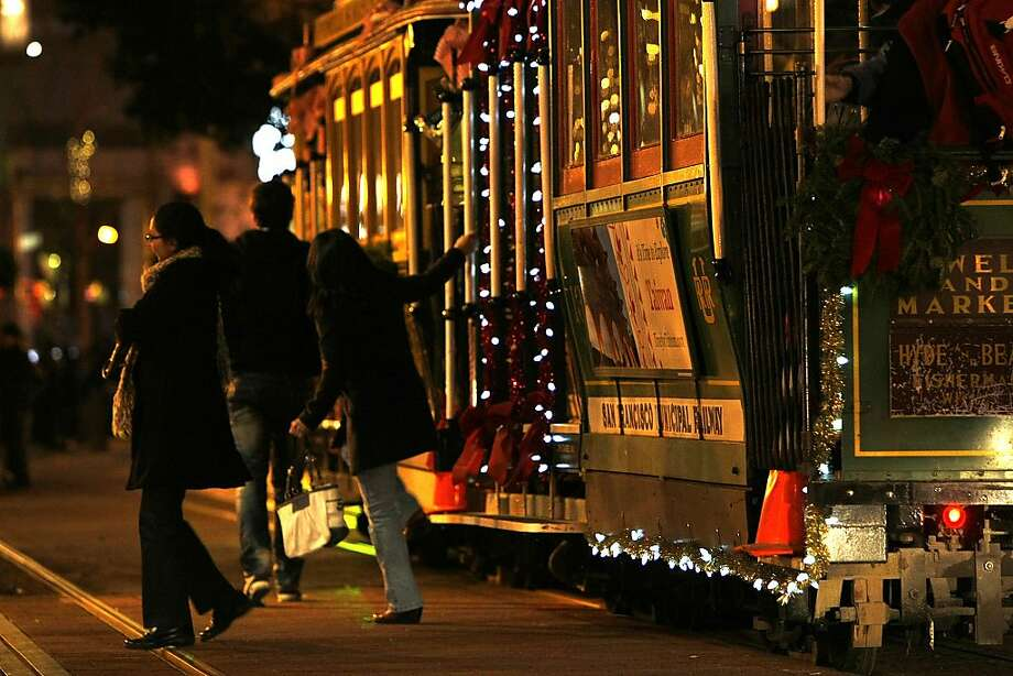 Riders hop off a cable car that has been all decked out in holiday finery in keeping with the season. Photo: Sean Havey, The Chronicle