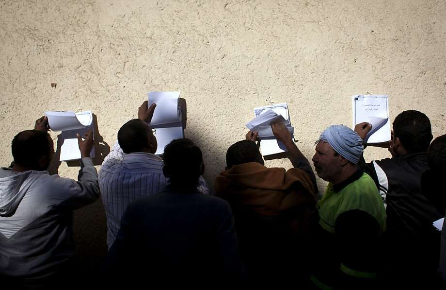 Egyptians check voter lists outside a polling station in Giza during a referendum on a new constitution. Photo: Nasser Nasser, Associated Press