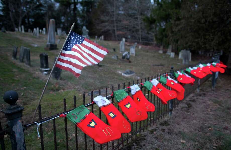 Twenty-six Christmas stockings hang on the fence at the Sandy Hook Cemetery across from the entrance to the Sandy Hook School on Saturday, December 22, 2012. A week earlier the school was the scene of a shooting that killed 20 students and six staff members. Photo: Joshua Trujillo, Joshua Trujillo/Hearst Newspaper / News-Times