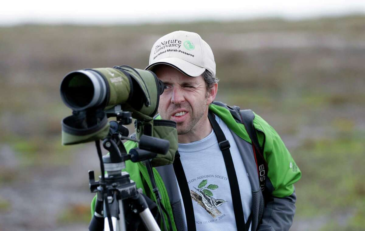 In this Monday, Dec. 17, 2012 photo, Rich Kostecke, a bird expert and associate director of conservation, research and planning at the Nature Conservancy in Texas, looks through his spotting scope during an annual 24-hour Christmastime ritual to count birds along the Texas Gulf Coast in Mad Island, Texas. The data collected, with the help of more than 50 other volunteers spread out into six groups across the 7,000-acre Mad Island preserve, will be regionally and nationally analyzed, landing in a broad database that includes results from hundreds of other bird counts going on nationally during a two week period. What began 113 years ago as an Audobon Society protest to annual bird hunts that left piles of carcasses littered in different parts of the country now helps scientists understand how birds react to short-term weather events, such as drought and flooding, and seek clues on how they might behave as temperatures rise and climate changes. (AP Photo/David J. Phillip)