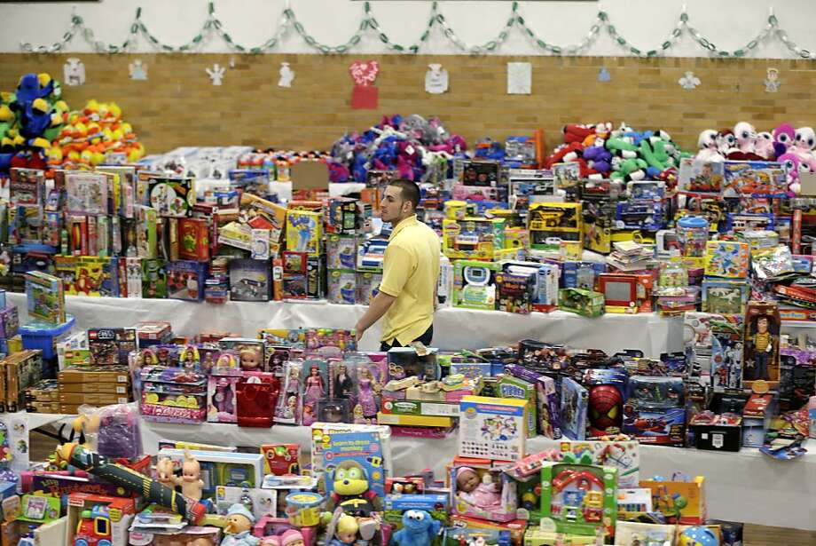 Volunteer Anthony Vessicchio helps sort tables full of donated toys at the town hall in Newtown. Photo: Seth Wenig, Associated Press