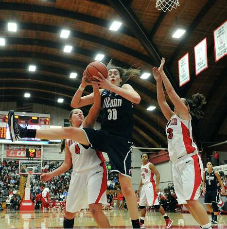 Connecticut's Breanna Stewart, center, snags a rebound while guarded by Hartford's Christie Michals, left, and Taylor Clark, right, during the second half of an NCAA women's college basketball game in West Hartford, Conn., Saturday, Dec. 22, 2012. Connecticut won 102-45. (AP Photo/Jessica Hill) Photo: Jessica Hill, Associated Press / FR125654 AP