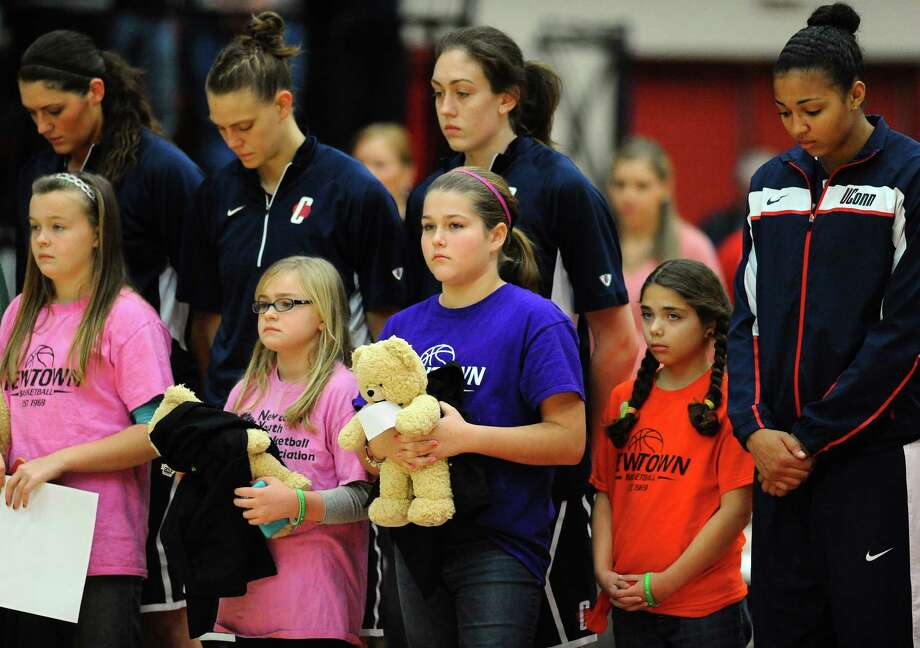 Members of Connecticut's women's basketball team stands with children from Newtown's Youth Basketball Association during a ceremony for the victims of the Sandy Hook Elementary School shooting before an NCAA college basketball game against the University of Hartford, Saturday, Dec. 22, 2012, in West Hartford, Conn. (AP Photo/Jessica Hill) Photo: Jessica Hill, Associated Press / FR125654 AP
