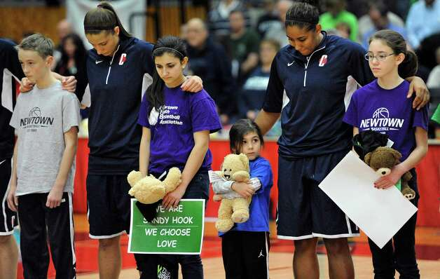 Connecticut's Caroline Doty, second from left, and Kaleena Mosqueda-Lewis, second from right, stands with children from Newtown's Youth Basketball Association during a ceremony for the victims of the Sandy Hook Elementary School shooting before an NCAA women's college basketball game against the University of Hartford, Saturday, Dec. 22, 2012, in West Hartford, Conn. (AP Photo/Jessica Hill) Photo: Jessica Hill, Associated Press / FR125654 AP