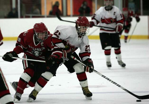 Greenwich High School's Matt Lodato, center, takes a hit from New Canaan's Puck Richardson but was still able to score one of the two goals against New Canaan in Saturday's game, Dec. 22, 2012.  New Canaan went on to win 4-2. Photo: DAVID AMES / GREENWICH TIME FREELANCE