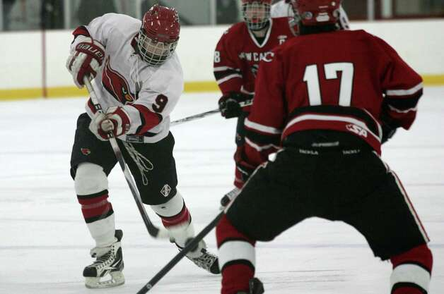 Greenwich High School's Alex Bastone, left, scored in the 2nd period of Saturday's, Dec. 22, 2012, game against New Canaan.  New Canaan went on to win 4-2. Photo: DAVID AMES / GREENWICH TIME FREELANCE
