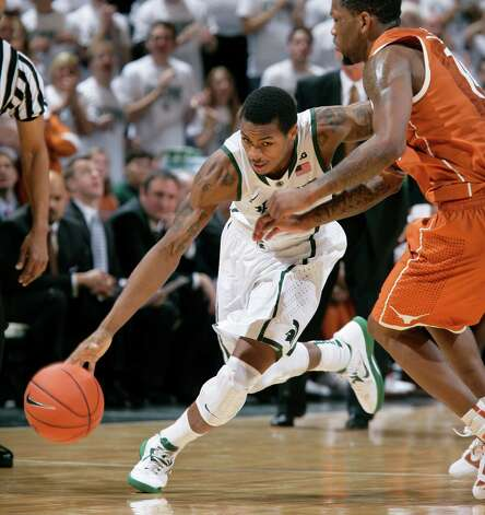 Michigan State's Keith Appling, left, drives against Texas' Julien Lewis during the second half of an NCAA college basketball game, Saturday, Dec. 22, 2012, in East Lansing, Mich. Michigan State won 67-56. (AP Photo/Al Goldis) Photo: Al Goldis, Associated Press / FR11125 AP