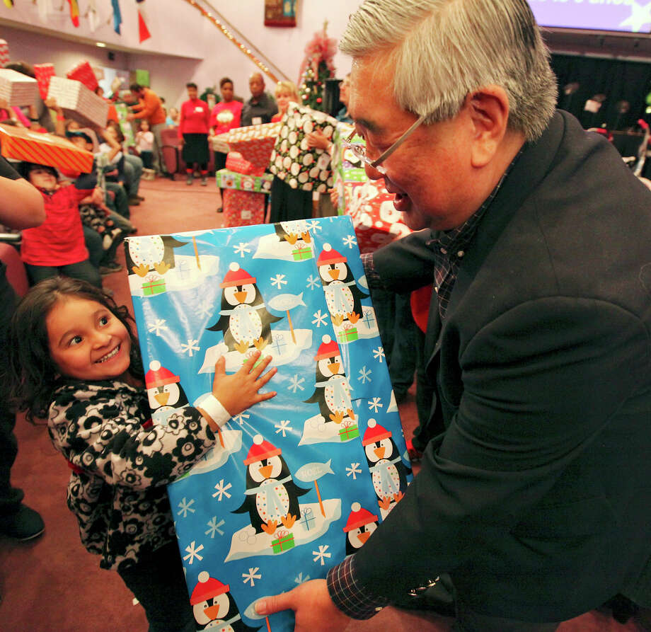 "Three-year-old America Herrera is all smiles as she's handed a gift by District Judge Peter Sakai during the Jarel's Toy Chest event at the New Life Christian Center. ""This event gets even bigger and better each year,"" the judge said. ""This is truly amazing and a blessing from God."" Photo: Edward A. Ornelas, San Antonio Express-News / © 2012 San Antonio Express-News"
