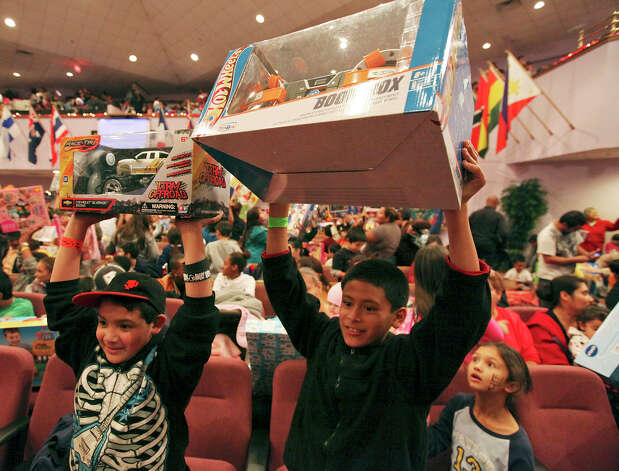 Nine-year-old David Perez (left) and his cousin Juan Mann, 11, show off their gifts at Jarel's Toy Chest. The event, which began with about 100 gifts being given away, now tops 2,000. Photo: Edward A. Ornelas, San Antonio Express-News / © 2012 San Antonio Express-News