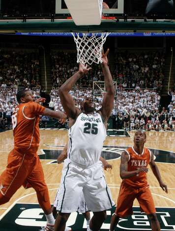 Michigan State's Derrick Nix (25) shoots between Texas' Cameron Ridley, left, and Sheldon McClellan during the first half of an NCAA college basketball game, Saturday, Dec. 22, 2012, in East Lansing, Mich. Nix led Michigan State with 25 points and 11 rebounds in a 67-56 win. (AP Photo/Al Goldis) Photo: Al Goldis, Associated Press / FR11125 AP
