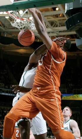 Texas' Cameron Ridley, right, dunks as he is fouled by Michigan State's Derrick Nix during the first half of an NCAA college basketball game, Saturday, Dec. 22, 2012, in East Lansing, Mich. (AP Photo/Al Goldis) Photo: Al Goldis, Associated Press / FR11125 AP