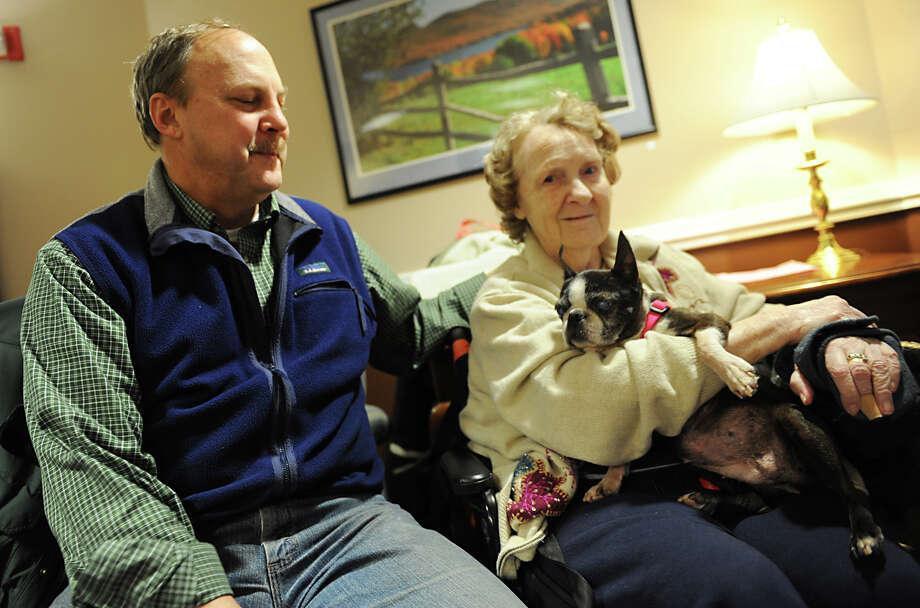 Bruce Williamson talks about Verizon phone service while sitting with his mother, Marilyn Williamson, and their dog Annabelle at Schaffer Heights, Friday, Dec. 21, 2012 in Schenectady, N.Y. (Lori Van Buren / Times Union) Photo: Lori Van Buren