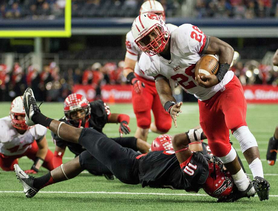 Katy running back Adam Taylor (28) breaks the tackle of Cedar Hill defensive back Ronald Jones (10) on a 17-yard touchdown run during the first half of the Class 5A Division II state championship football game at Cowboys Stadium on Saturday, Dec. 22, 2012, in Arlington. Photo: Smiley N. Pool, Houston Chronicle / © 2012  Houston Chronicle