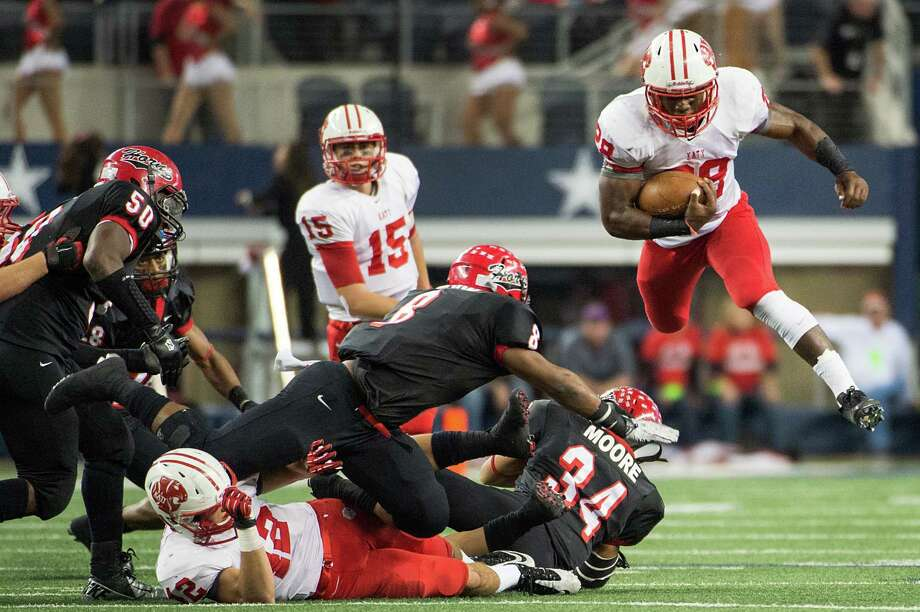 Katy running back Adam Taylor (28) leaps over Cedar Hill linebacker Richard Moore (34) during the first half of the Class 5A Division II state championship football game at Cowboys Stadium on Saturday, Dec. 22, 2012, in Arlington. Photo: Smiley N. Pool, Houston Chronicle / © 2012  Houston Chronicle