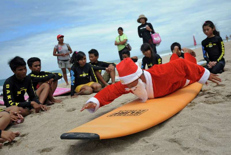 A Balinese surfer dressed in a Santa Claus outfit trains children before their surf outing on Kuta b