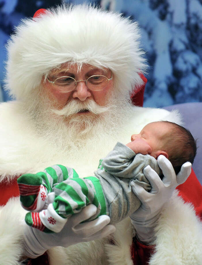 A man dressed as Santa Claus holds 1-week-old Zachary Nicolson for a Christmas visit at Twelve Oaks Mall on Saturday, Dec. 22, 2012, in Novi, Mich. Photo: Bryan Mitchell, Associated Press / The Detroit News