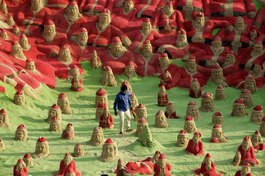 Indian Sand artist Sudersan Pattnaik works on a sand sculpture with over 500 Santa Claus statues at  Golden Beach in Puri on about 65 kilometres away from Bhubaneswar on December 22, 2012. Christmas is celebrated on December 25 all over world. Photo: STRDEL, AFP/Getty Images / AFP