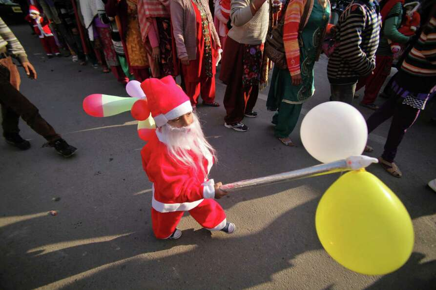 A young child dressed as Santa Clause walks with balloons during a Christmas procession in Jammu, In