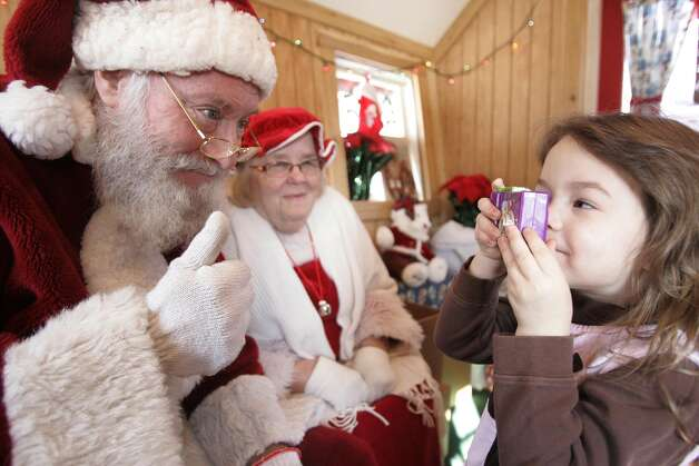 Santa gives a thumbs up to a young photographer as she takes Santa's photo with a toy camera as young boys and girls line up to visit Santa and Mrs Claus in their chalet Saturday December 22, 2012 in LaPorte, Ind. Photo: Bob Wellinski, Associated Press / The LaPorte Herald-Argus