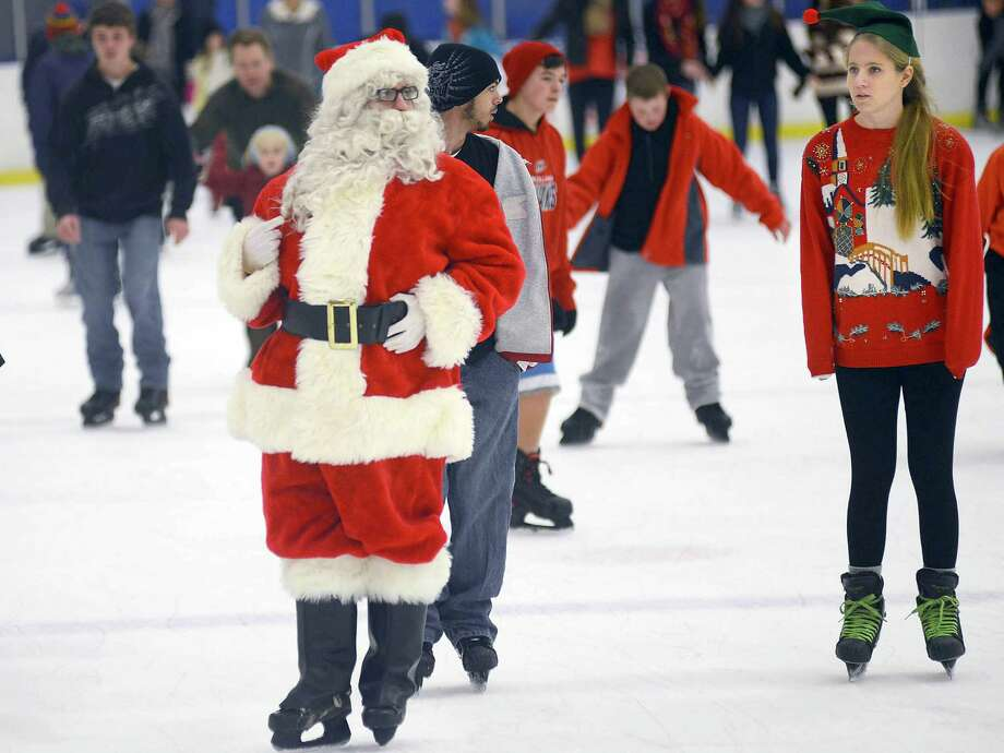 Santa skates  with his helper Lindsey Perry, right, at the Orange County Sportsplex, in Hillsborough,N.C., Saturday  December 22, 2012, during a public session of Skate with Santa for the holiday. Photo: Bernard Thomas, Associated Press / The Herald-Sun