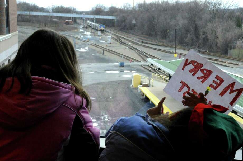 Ten-year-old Madeline Demers and  5-year-old sister Julianna of East Greenbush watch out the window of the Amtrak station as a train arrives from NYC with their aunt Anna aboard in Rensselaer, N.Y., Saturday Dec. 22 2012. (Michael P. Farrell/Times Union) Photo: Michael P. Farrell