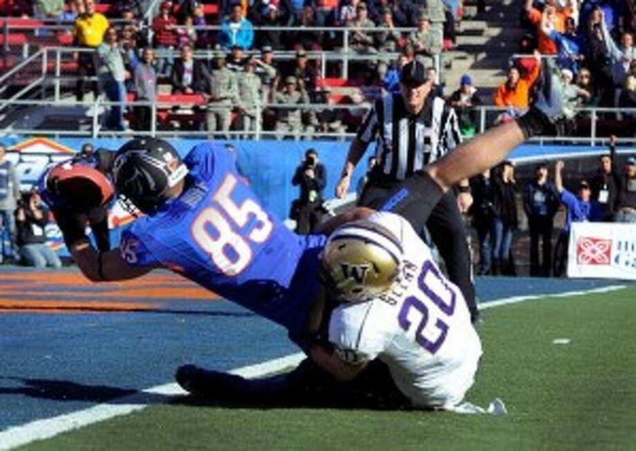 Boise State tight end Holden Huff rolls over UW safety Justin Glenn as he scores a touchdown in the first half Saturday. (David Becker/AP Photo)