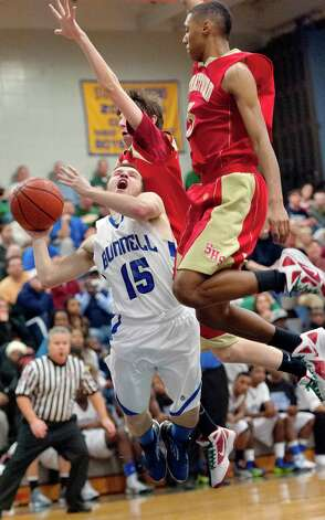 Stratford high school's Emmanuel Young and Arron Smith try to stop Bunnell high school's Timothy White from going up for a shot in a boys basketball game played at Bunnell high school, Stratford, CT on Saturday, December 22nd, 2012. Photo: Mark Conrad / Connecticut Post Freelance
