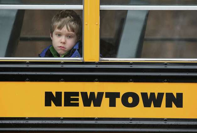 A child gazes from a school bus as it passes by the St. Rose of Lima Catholic church while mourners gathered for a funeral service for shooting victim Jessica Rekos, 6, on December 18, 2012 in Newtown, Connecticut. Four days after 20 children and six adults were killed at Sandy Hook Elementary School, most students in Newtown returned to school. Children at Sandy Hook Elementary will attend a school in a neighboring town until authorities decide whether or not to reopen their school.  (Photo by Jo