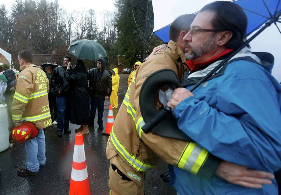 A fire rescue official, second from right, gives a hug to a person after a group of people paused for a moment of silence at a makeshift memorial near the main road that leads into Sandy Hook Elementary School during a memorial at 9:30 a.m.,  Friday, Dec. 21, 2012, in Newtown, Conn. The chiming of bells reverberated throughout Newtown, commemorating one week since the crackle of gunfire in a schoolhouse killed 20 children and six adults in a massacre that has shaken the community and the nation (AP Photo/Julio Cortez) Photo: Julio Cortez, ASSOCIATED PRESS / Associated Press