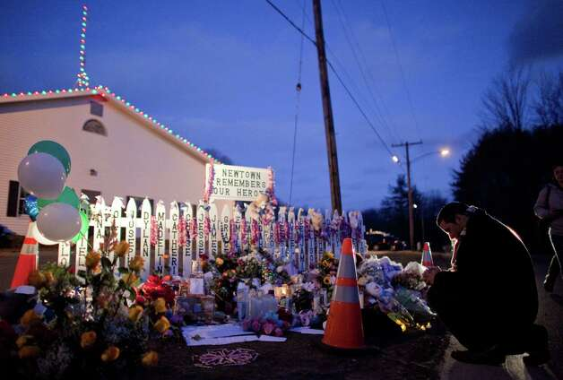A mourner kneels in front of a memorial on the road leading to the Sandy Hook Elementary School on Saturday, December 22, 2012. Significant crowds came to Sandy Hook to pay respects to the people killed in last weeks shooting rampage. Photo: Joshua Trujillo, Joshua Trujillo/Hearst Newspaper / The News-Times